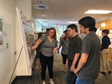 Rachel Walker (center) explains her Summer REU 2019 math research (Photo by Yasmine Bassil)