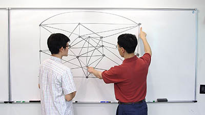 Yan Wang (left) and Xingxing Yu (right) at the whiteboard.